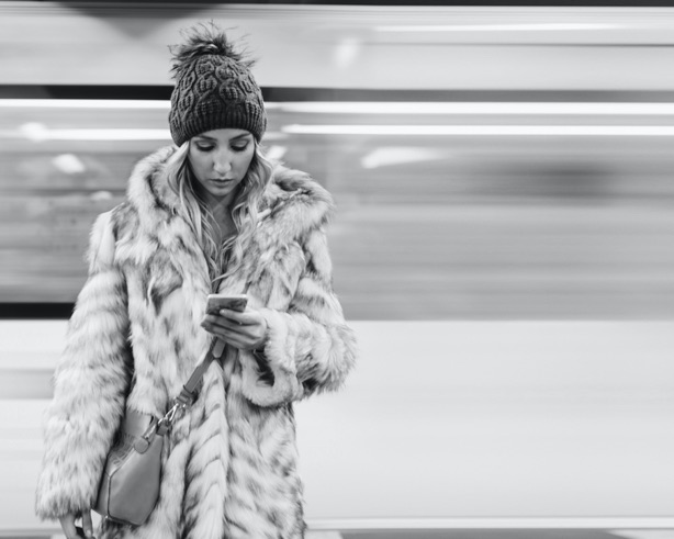 Woman looking at her phone on a station platform as a train passes